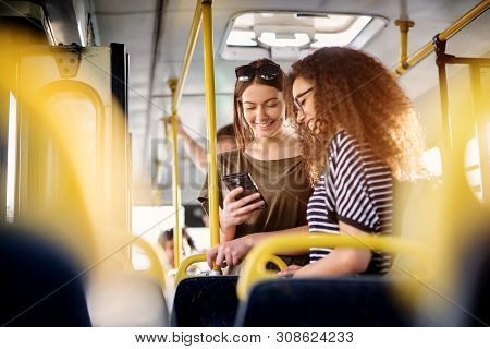 Two Cheerful Pretty Young Women Are Standing In A Bus And Looking At The Phone And Smiling While Wai