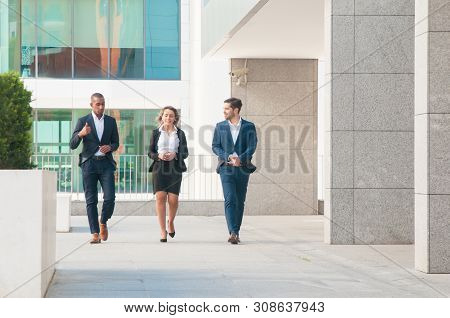 Confident Business Colleagues Walking Outdoors And Talking. Friendly Business People Chatting On The