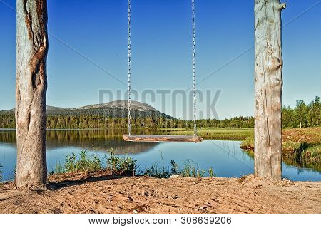 A Wooden Swing Hangs By The Still Water Of A Beautiful Lake At The Finnish Lapland. It Is Midsummer
