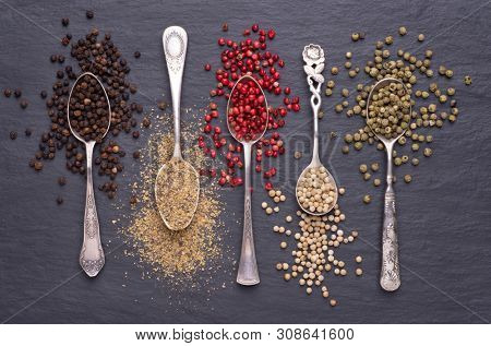 Various kinds of peppercorns in silver spoons on black stone background