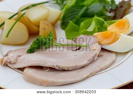 Roast pork slices with baby new potatoes a leafy salad and hard-boiled eggs