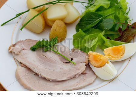 High angle view of cold roast pork slice dinner with salad leaves, chives, egg and boiled new potatoes