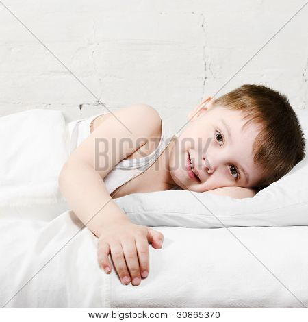 Boy Smiling In Bed