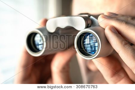 Man Watching Out The Window With Binoculars. Curious And Nosy Neighbour. Private Detective Or Underc