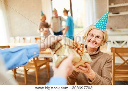 A senior as a birthday child is happy about a present at her birthday party
