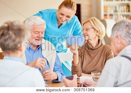 Nursing lady looks curious while playing cards of seniors in retirement home