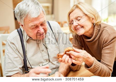Senior pensioner couple in retirement home has fun with a wooden puzzle patience game