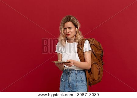 Portrait Of A Girl With Curly Blond Hair, Orange Backpack And White Headset Dressed In A White T-shi