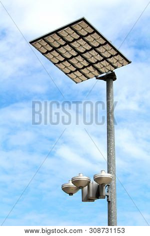 Modern LED street light reflectors in protective case pointed towards large reflective panels mounted on top of strong metal pole on cloudy blue sky background poster
