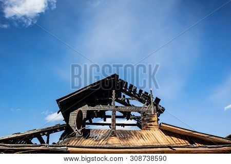 Burnt Roof Of A Wooden House Against The Blue Sky. The Concept Of Home Insurance Against Accidents,