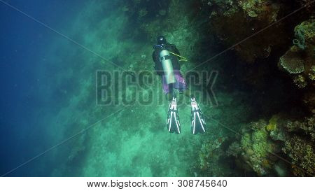 Scuba Diver Explores Underwater Coral Reef And Watching Fish.scuba Diver Underwater In Tropical Sea.