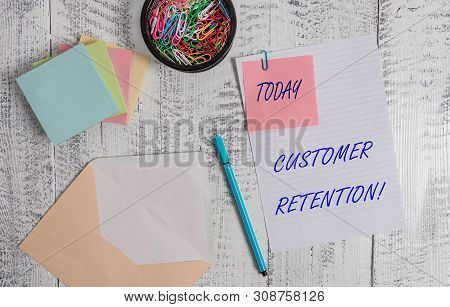 Handwriting text writing Customer Retention. Concept meaning Keeping loyal customers Retain analysisy as possible Envelope sheet paper sticky note pads pen clips holder wooden background. poster