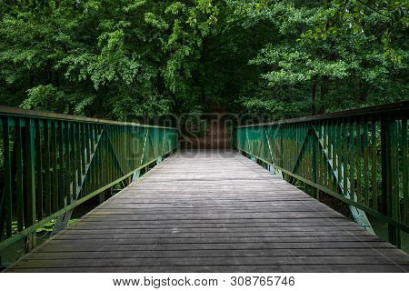 Footbridge Over The Water Leading To The Park. Passage Over The Water In The Forest Area. Season Of