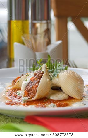 Pasta Shell Conchiglioni With Minced Meat Filling In Sauce Close-up In Dish. Depth Of Field.