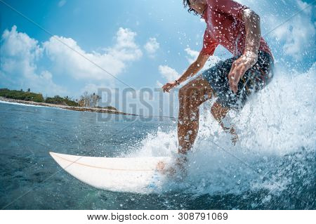 Young caucasian man surfs the ocean wave and makes a lot of splashes into the camera. Chickens surf spot in Maldives