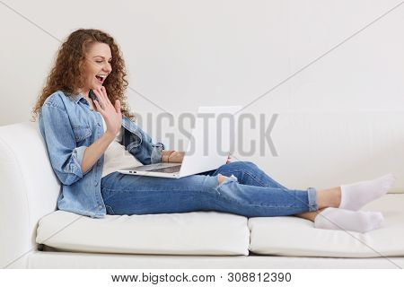 Indoor Shot Of Emotional Curly Haired Lady Sitting On Sofa, Opening Her Mouth Widely, Making Gesture