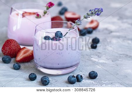 Strawberry, Blueberry Smoothie On Light Background Decorated Lavander And Rose . Milkshake With Fres