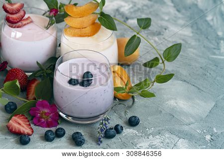 Strawberry, Blueberry, Apricot Smoothie On Light Background Decorated With Leaves. With Fresh Berrie