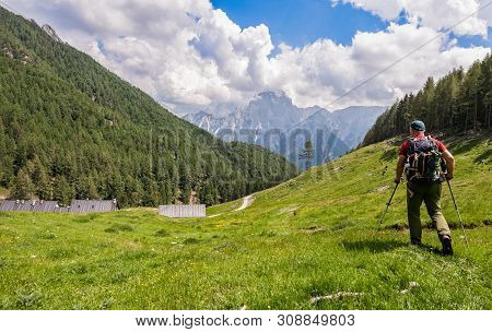 Hiker Walk On Trail And Admiring The Panorama. Italy Alps.