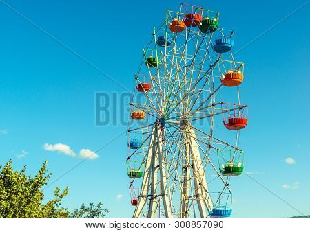 Scenic View Of Beautiful Ferris Wheel In Amusement Park. Large Colorful Ferris Wheel On The Blue Sky