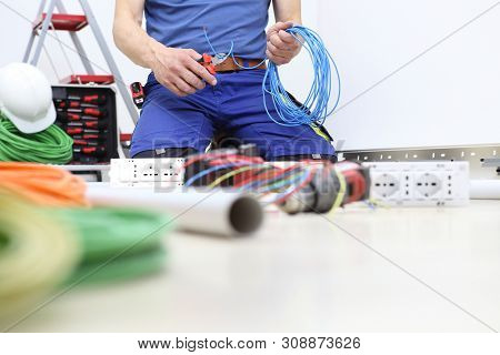 electrician at work with nippers in hand cut the electric cable, install electric circuits, electrical wiring poster
