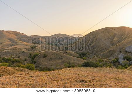 Hilly And Mountainous Steppe Under The Rays Of The Early Sun With Yellowed Dry Grass