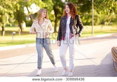 Outdoors portrait of two delightful young woman. Two caucasian girls friend stroll and chat together in sunny day. Friendship. poster