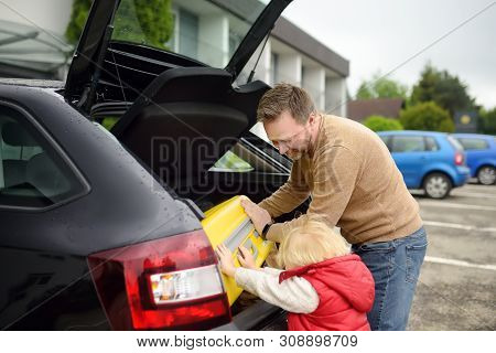Handsome Man And His Little Son Going To Vacations, Loading Their Suitcase In Car Trunk. Automobile