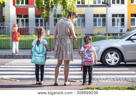 Back To School Education Concept With Girl Kids, Elementary Students, Carrying Backpacks Going To Cl