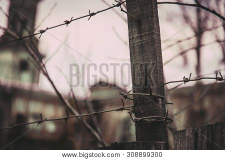 Old Wooden Fence With Rusty Nails And Barbed Wire