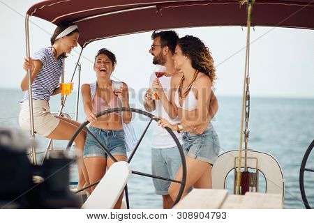 Smiling friends sitting on sailboat deck and having fun. Vacation, travel, sea, friendship and people concept.