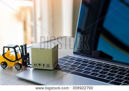 Mini Forklift Truck Load Cardboard Box With Symbols On Laptop Keyboard. Logistics And Transportation