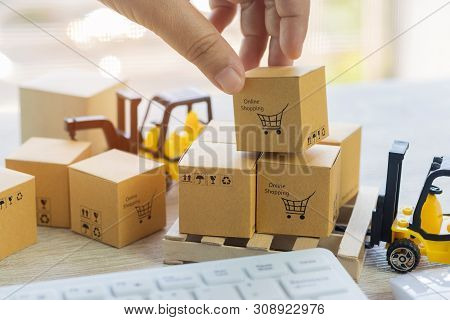 Mini Forklift Truck Load Cardboard Boxes With Symbols On Wood Pallet And Fingers Over Its And Keyboa