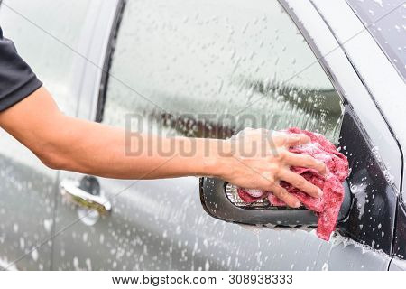The Man Wash The Sideview Mirror Of The Car