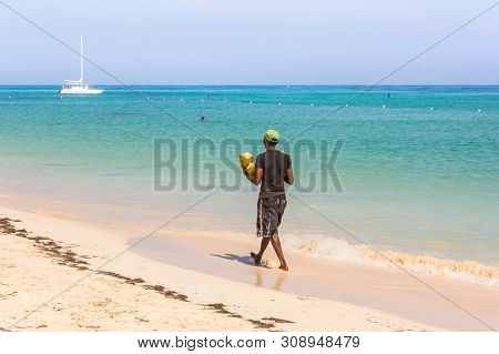 Man With Coconuts Walk On The Beach