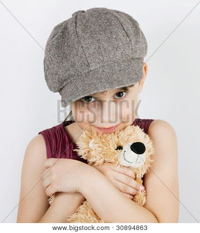 Girl in gray cap gown holding a teddy bear in hands poster
