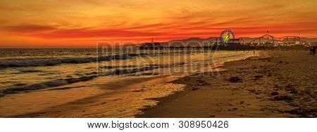 Amazing Landscape Of Iconic Santa Monica Pier At Orange Red Sunset Sky From Beach On Paficif Ocean.