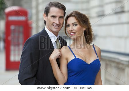 Romantic man and woman couple by a traditional red phone box, London, England, Great Britain