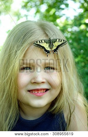 Butterfly Sitting On A Child. Child With A Butterfly. Butterfly Machaon On A Little Girl. Selective