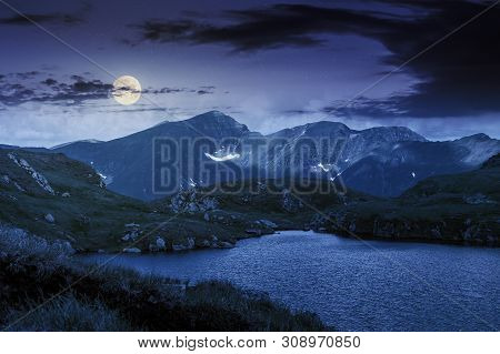 Alpine Glacier Capra Of Fagaras Mountains At Night In Full Moon Light. Gorgeous Summer Landscape. Go