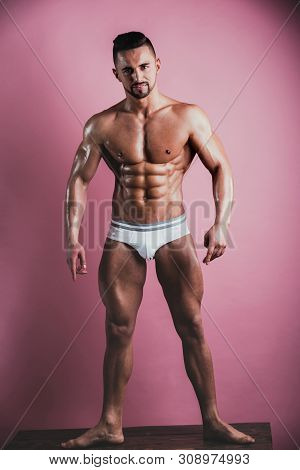 Muscular Handsome Athletic Man Stands On Pink Background And Looks At Camera. Great Example Of Perfe