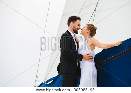 Handsome Man And Attractive Woman Smiling And Kissing Embracing On Yacht In Bright Day