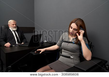 Disappointed Woman With Indicators On Fingers Answering Questions During Lie Detector Test. Female S