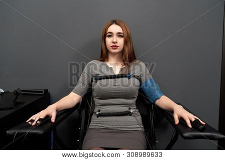 Front View Of Frightened Woman Sitting On Chair While Lie Detector Measuring Pulse. Female Adult Wit