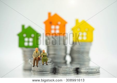 Miniature People: Happy Old People Standing With Home, Retirement Planning, Emergency Plan And Life