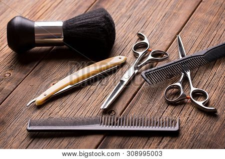 Barber Tool On A Wooden Table. Scissors, Comb For Hair And A Razor Close-up. Hairdressing Tool Kit.