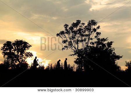 Three Men Walking in Sunset Sky