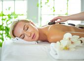 Young woman in spa salon, getting stones massage poster