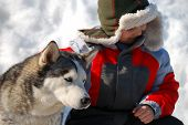 Winter portrait of a young boy with his husky dog snow in the background. poster