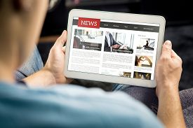 Online News Article On Tablet Screen. Electronic Newspaper Or Magazine. Latest Daily Press And Media